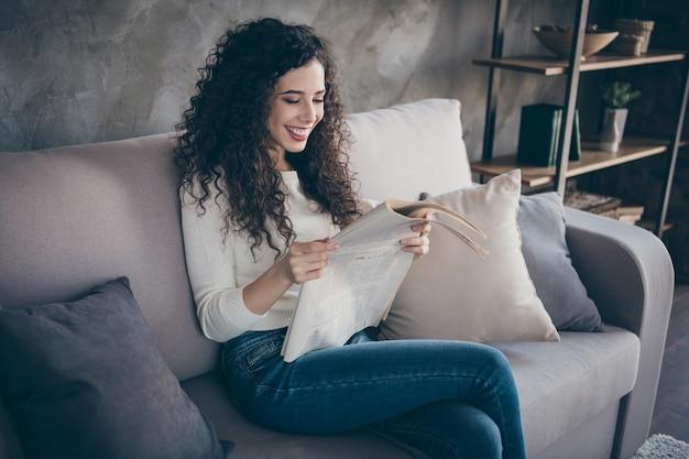 Портрет жизнерадостной девушки, сидящей на диване и читающей мировые новости в современном индустриальном стиле лофта в помещении