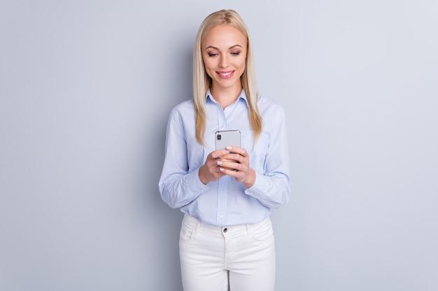 Портрет жизнерадостной девушки использует экран смартфона на серой стене