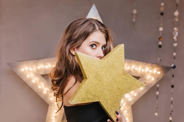 Портрет жизнерадостной девушки с вьющимися волосами в черном топе, закрывающей лицо золотой звездой
