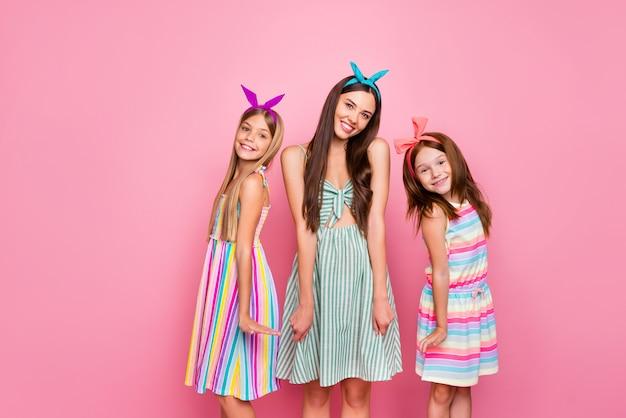 ピンクの背景に分離されたスカートのドレスを着てポーズをとって笑っているカラフルなヘッドバンドと陽気な女の子の肖像画