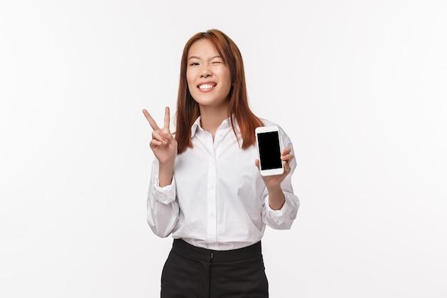 白いシャツ、スカート、ウィンク、笑顔で陽気な見栄えの良いアジアの女性の肖像画、平和のかわいいサインを示す電話アプリケーション、携帯電話のディスプレイ、白い壁を紹介