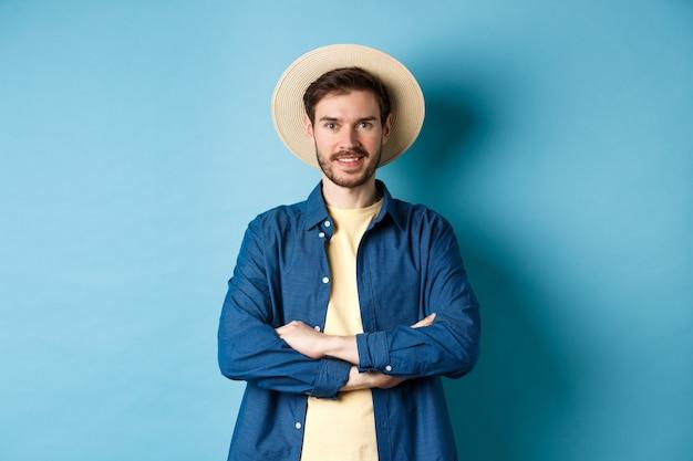Портрет веселого парня, идущего в отпуск в соломенной летней шляпе, скрестив руки на груди и улыбающегося, уверенно выглядящего, стоя на синем фоне.