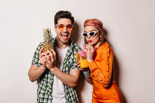 Портрет веселого парня в оранжевых очках, держащего ананас, и его подруга в атласном платье, пьющая коктейль на белом пространстве.