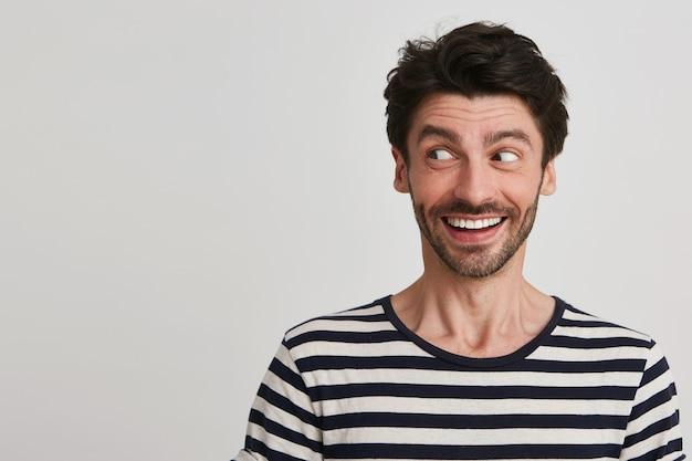 Портрет веселого красивого бородатого молодого человека в полосатой футболке улыбается и смотрит в сторону, изолированную на белом