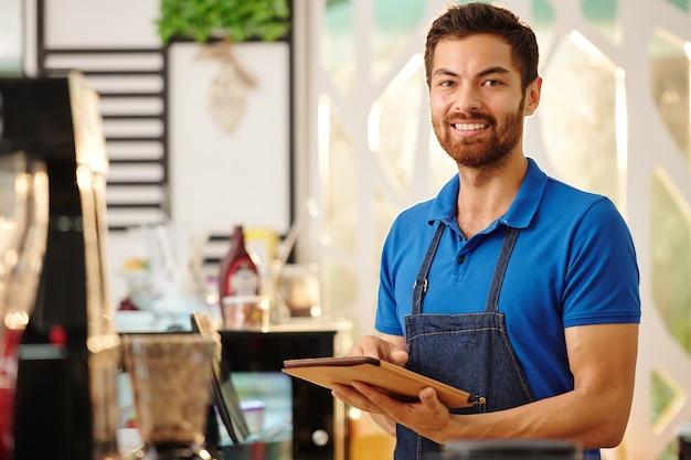Портрет веселого красивого официанта кофейни, стоящего с планшетным компьютером в руках и улыбающегося в камеру
