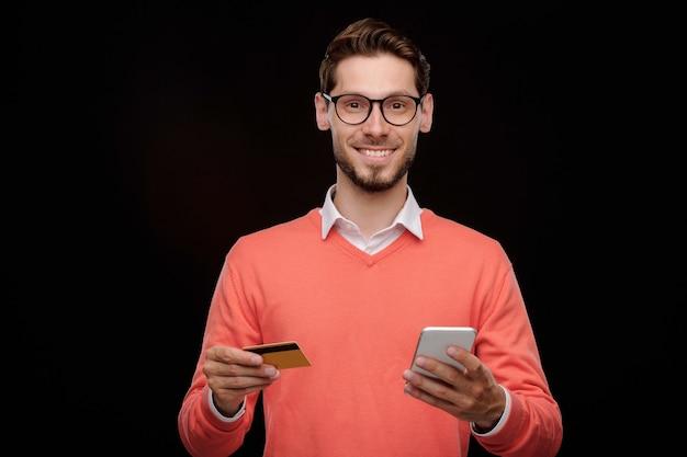 신용 카드와 스마트 폰으로 서서 온라인 거래 서비스를 사용하는 수염을 가진 쾌활한 잘 생긴 젊은 남자의 초상화