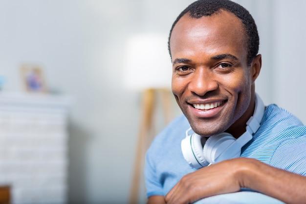 Портрет веселого счастливого приятного человека, улыбающегося и смотрящего на вас в наушниках