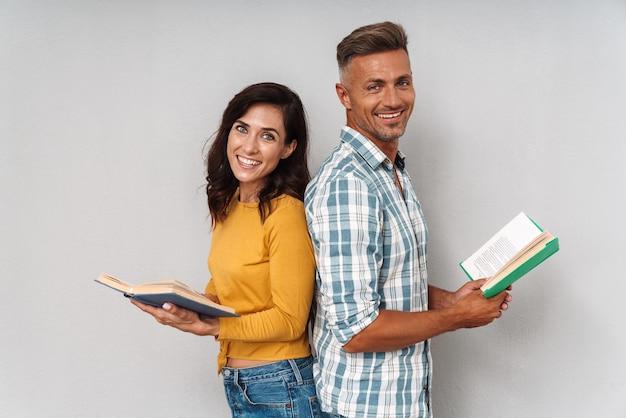 Портрет веселой счастливой улыбающейся взрослой любящей пары, изолированной над серой стеной, читающей книгу.