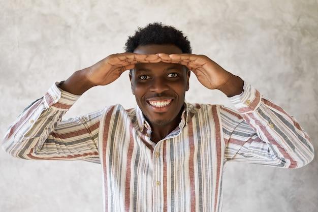 明るい未来に興奮して、彼の額に両手を保持し、広く笑顔で遠くを見ているカジュアルなシャツを着た陽気な幸せな若いアフリカ系アメリカ人の男の肖像画。ボディランゲージ