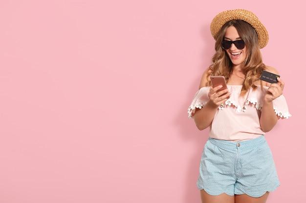 Портрет веселой счастливой молодой женщины, носящей лето светло-розовая блузка, синие шорты, черные очки и соломенная шляпа, держащая пластмассовую кредитную карту, используя мобильный телефон. скопируйте место для рекламы.