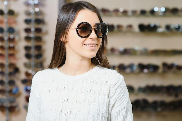 Портрет веселой нерешительной женщины в магазине оптики