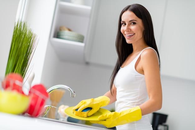 おいしい夕食後の陽気な主婦のきれいな皿の肖像画は、屋内のキッチンハウスでスポンジ手袋の洗浄プレートを使用します