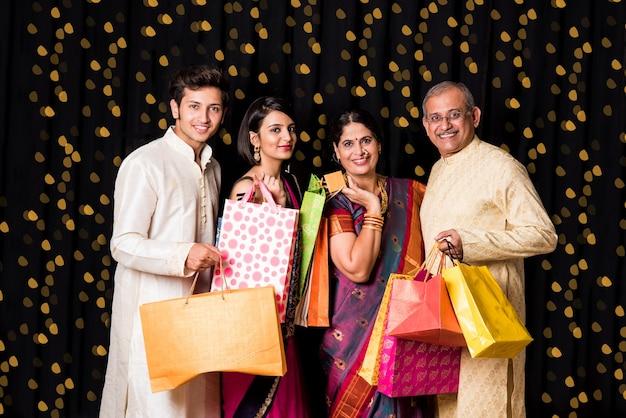 Bokeh와 검은 배경 위에 절연 디 왈리에서 전통적인 착용에 쇼핑백과 쾌활 한 인도 가족의 초상화