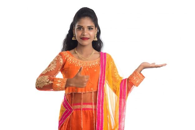 Портрет жизнерадостной индийской традиционной молодой женщины представляя что-то под рукой, показывая космос экземпляра на ее ладони на белой стене