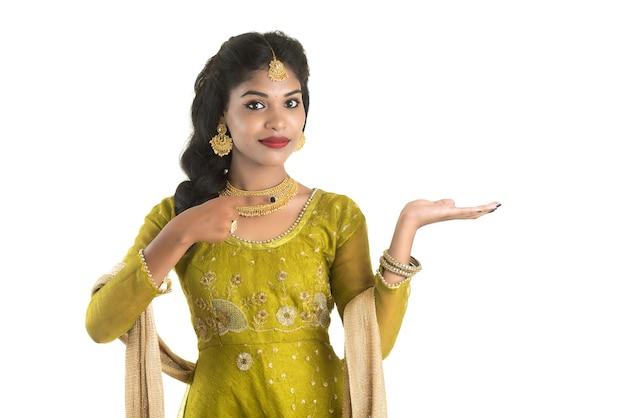 白地に彼女の手のひらにコピースペースを示す、何かを提示する陽気なインドの伝統的な若い女性の肖像画
