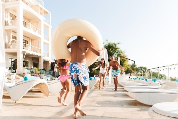 Портрет веселых детей и родителей, идущих возле бассейна и несущих резиновое кольцо возле отеля во время отпуска