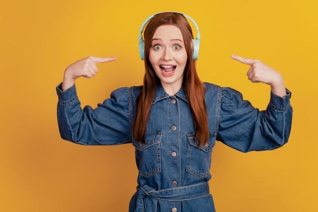 헤드폰을 끼고 있는 쾌활한 여성의 초상화는 노란색 배경에서 음악을 직접 듣습니다.
