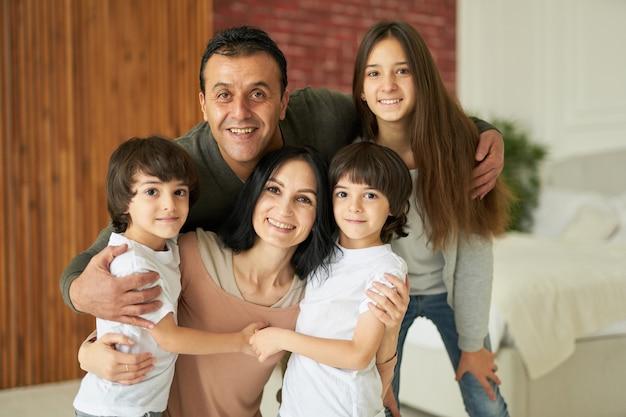 Портрет веселой латинской семьи, девочки-подростка и маленьких мальчиков-близнецов, улыбаясь в камеру, позируя со своими родителями в помещении. семья, концепция детства
