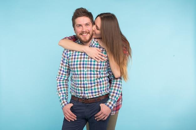 青い背景に浮気する陽気な笑う面白い若い恋人たちの肖像画