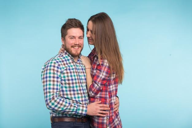 青い壁に浮気する陽気な笑い面白い若い恋人たちの肖像画。
