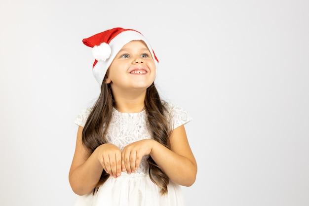 빨간 산타 클로스 모자를 쓰고 물결 모양의 머리를 가진 쾌활한 웃는 소녀의 초상화는 랍비의 발을 보여줍니다 ...