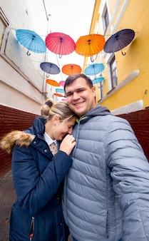 Портрет веселой смеющейся молодой пары, позирующей на улице против разноцветных зонтиков, висящих между старыми зданиями