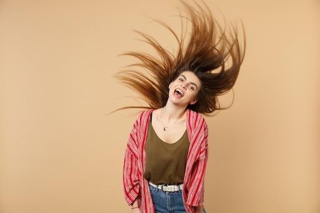 パステルベージュの壁の背景に分離された羽ばたき髪で浮気するカジュアルな服を着て陽気な笑う若い女性の肖像画。人々の誠実な感情のライフスタイルの概念。コピースペースをモックアップします。