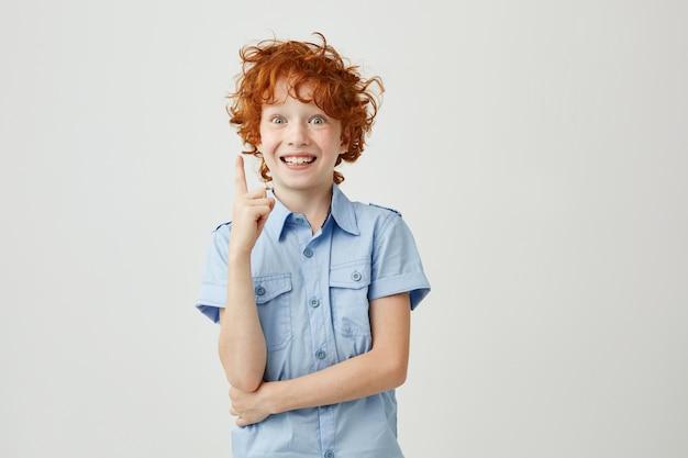 Портрет веселый маленький мальчик с рыжими волосами и веснушки улыбается, указывая вверх ногами с пальцем, имея сумасшедший выражение. копировать пространство
