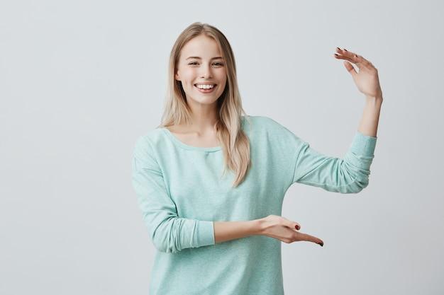 現在のボックスのサイズを示す白い歯で広く笑っているブロンドの髪を持つ陽気な素敵な白人女性の肖像画。ボディーランゲージと顔の表情