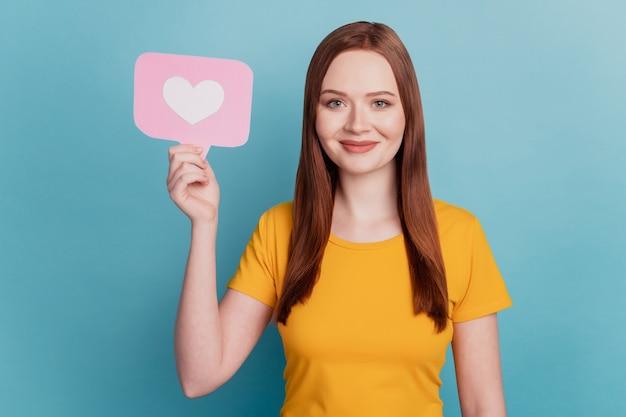 쾌활한 사랑스러운 여성의 초상화는 파란색 배경에 카드와 같은 심장 아이콘을 들고