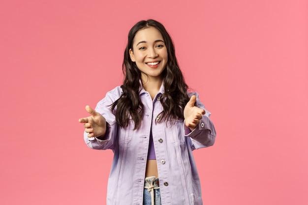 Портрет веселой, милой девушки разного роста в джинсовой куртке, уличной одежде, протягивающей руки к камере, желающей кого-то подержать или обнять, смотрящей на очаровательную вещь, радостно улыбаясь, розовый фон.