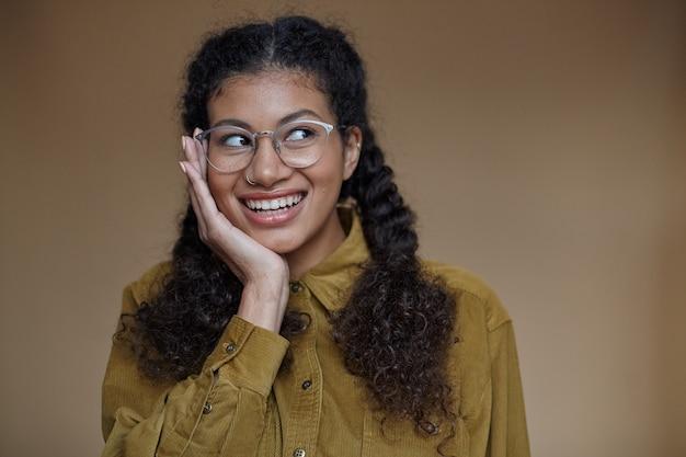 Портрет веселой милой молодой кудрявой темнокожей женщины с плетеной прической, держащей рукой подбородок и радостно смотрящей в сторону, в горчице