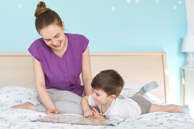 陽気な素敵な若い母親の肖像画は彼女の息子のおとぎ話を読みます