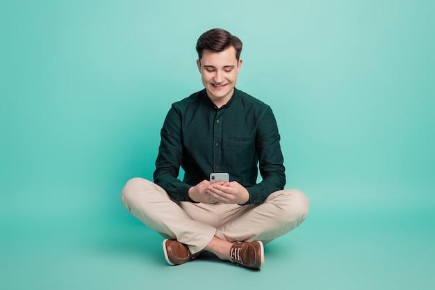 Портрет жизнерадостного мужчины держит телефон, смотрит экран, делится сообщениями в социальных сетях на бирюзовом фоне
