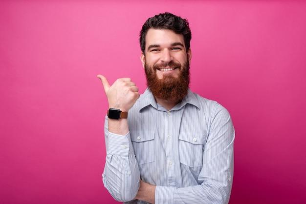 コピースペースを指しているシャツのひげと陽気な男の肖像画