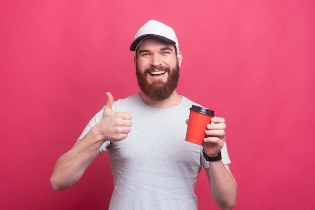 Портрет жизнерадостного человека с бородой показывает палец вверх жестом и держит чашку кофе, чтобы пойти