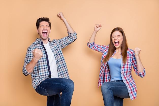 Портрет веселой супружеской пары поднимает кулаки, кричит, да, наслаждайтесь победой в лотерее, чувствую, радуйтесь, носите клетчатую рубашку, изолированную на пастельном цветном фоне