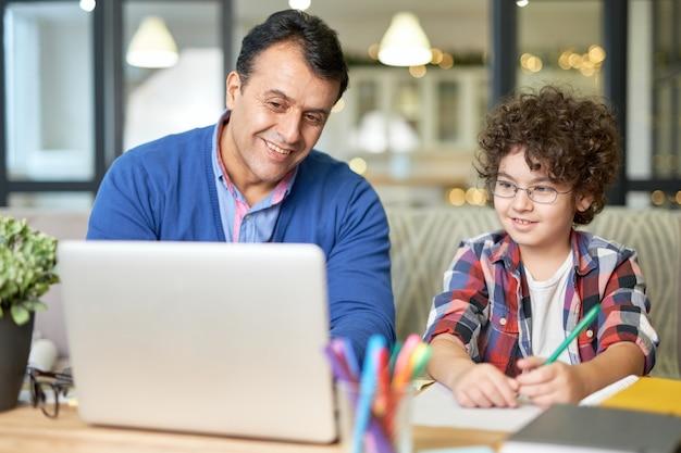 彼の息子と一緒に時間を過ごしている陽気な中年のヒスパニック系の父の肖像画。お父さんと一緒に机に座って、ノートパソコンを使って宿題をしている男の子。オンライン学習、家族の概念