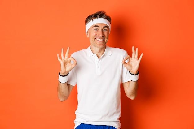 쾌활한 중년 남성 운동 선수의 초상화, 기쁘게 웃고 괜찮은 징후를 보여주는