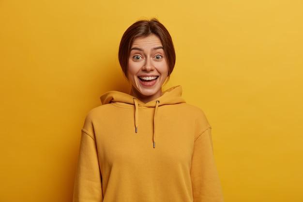 Портрет жизнерадостной миллениальной девушки радостно смеется, слышит приятные новости, носит толстовку с капюшоном, ведет непринужденную дружескую беседу, сияет белой улыбкой, позирует у желтой стены,