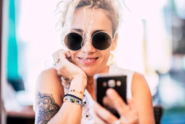 屋外で笑顔の携帯電話を使用して陽気な現代の若い女性の肖像画-携帯電話デバイスを見て楽しんでいるオンライン女性の人々-接続された幸せな女性
