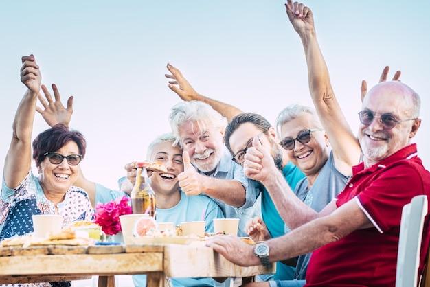 屋外のテーブルで食べ物や飲み物を楽しむことを祝う陽気な多世代家族の肖像画。ブランチをしながら一緒に充実した時間を過ごすことを親指をあきらめる興奮した家族の応援