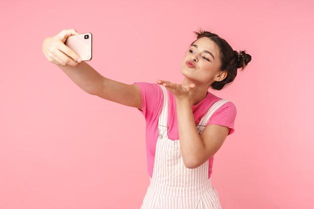携帯電話で自分撮りを取り、ピンクの壁に隔離されたエアキスを送信する陽気な素敵な女の子の肖像画