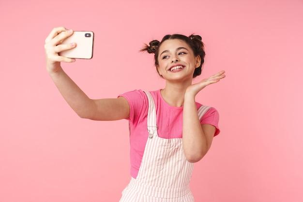 携帯電話でselfieを取り、ピンクの壁に孤立した笑顔の陽気な素敵な女の子の肖像画
