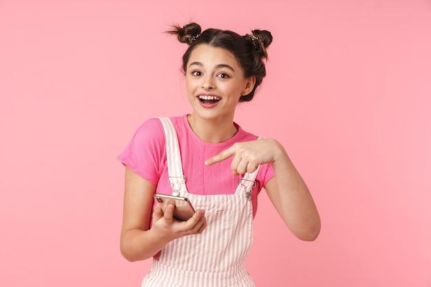 ピンクの壁に隔離された携帯電話に鼻ピアスを保持し、指を指している陽気な素敵な女の子の肖像画