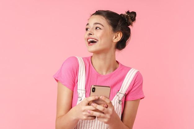 Портрет веселой симпатичной девушки с кольцом в носу, использующей мобильный телефон и смеющейся, изолированной над розовой стеной