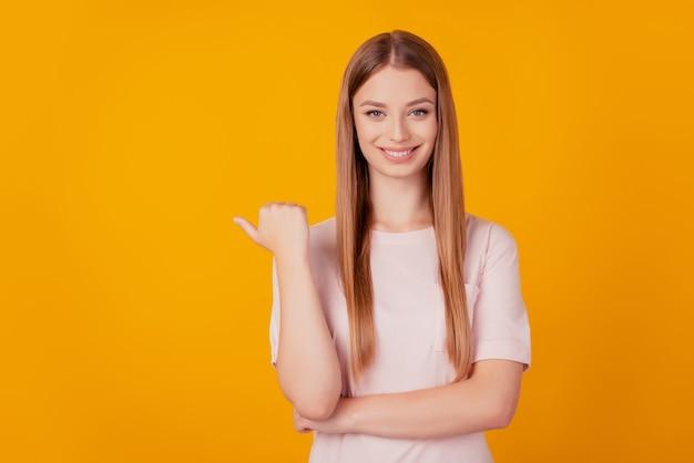 쾌활한 멋진 여성 엄지손가락의 초상화는 노란색 배경에 빈 공간을 직접 표시합니다.