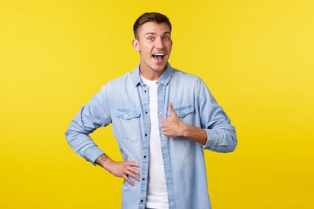 陽気な楽観的なハンサムな男の肖像画は、承認で親指を立てて、人々を励まします。かわいい男性の顧客は良い製品を評価し、同意するか何かが好きで、立っている黄色の背景は満足しています。
