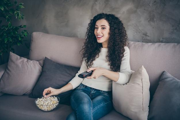 Портрет веселой мирной девушки, сидящей на диване и смотрящей телешоу в современном индустриальном стиле лофта