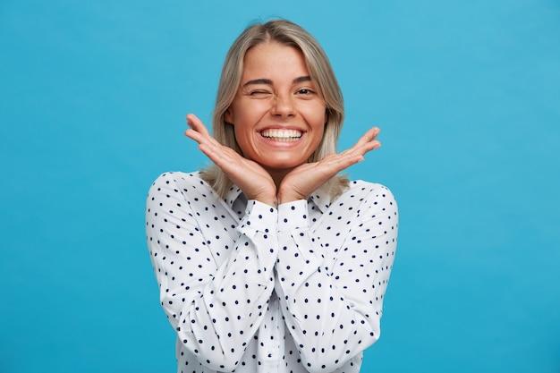 陽気な遊び心のある金髪の若い女性の肖像画は、青い壁に隔離されてウィンク、いちゃつく、楽しんでいる水玉シャツを着ています